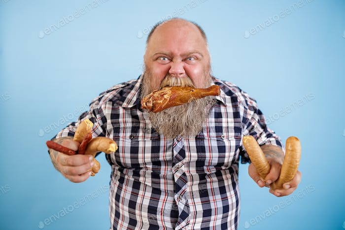 Greedy obese man holds chicken leg in teeth and bunches of sausages on blue background