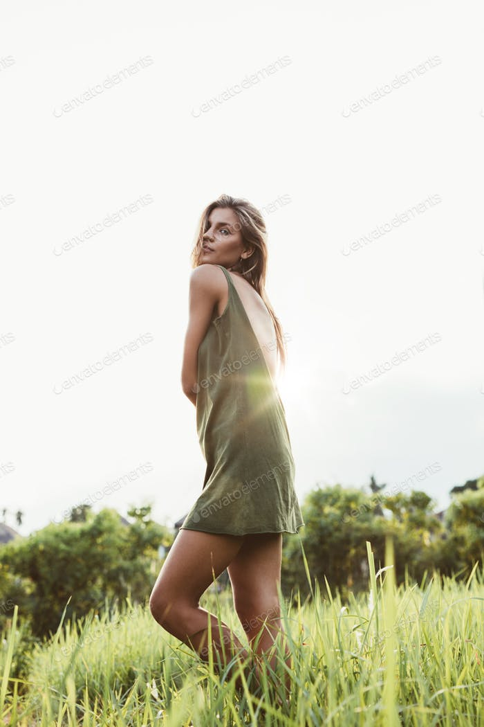 Young woman standing in field of grass