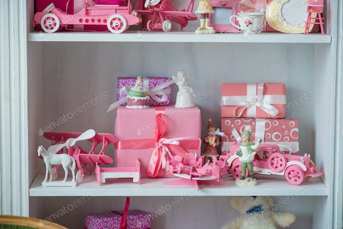 Christmas gifts in box on a shelf, pink car, airplane, wooden horse and gingle bell