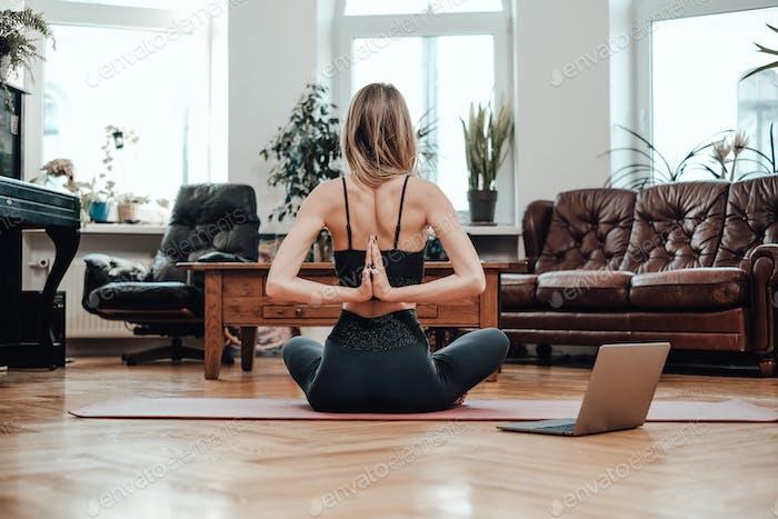 Rückansicht der Sportlerin, die Yoga auf dem Boden im Wohnzimmer macht