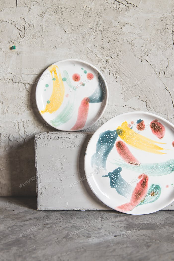 Ceramic plates painted in paints, on a gray background