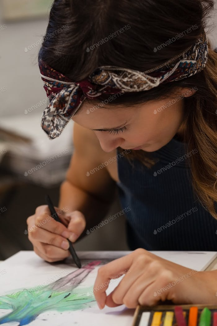 Woman drawing on book in drawing class