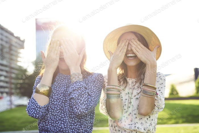 Two happy young woman covering their eyes with their hands