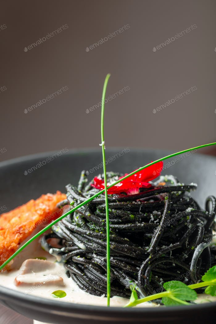 Fresh black tagliolini pasta with chicken in herbs on rucola and tomatoes