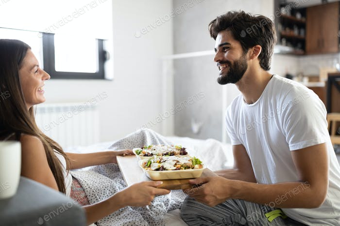 Happy young couple have breakfast at the bed. Care and romance at the morning