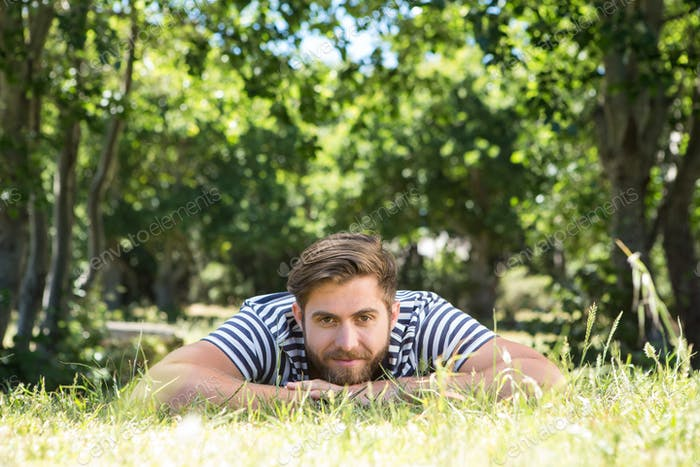 Hipster lying on the grass in the park on a summers day