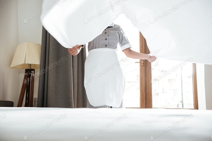 Cropped image of a hotel maid changing bed sheet