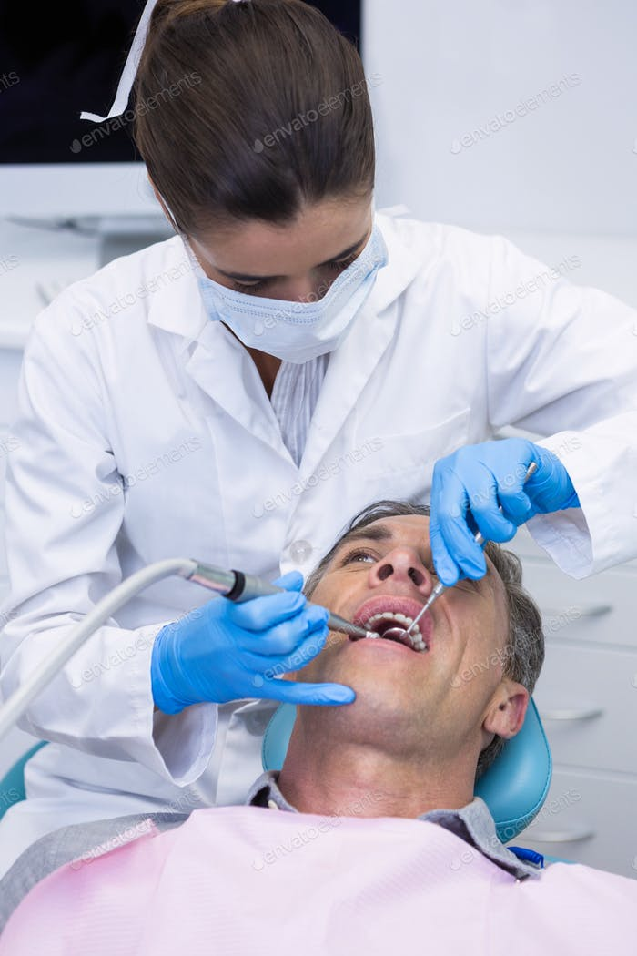 Dentist examining senior man mouth at medical clinic