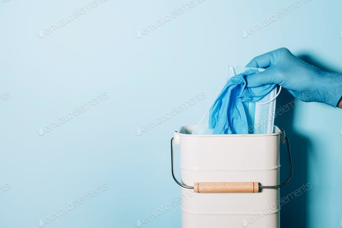 Hand in medical gloves throws medical mask into trash can on blue background. Quarantine over. Covid