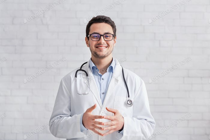 Remote work. Young doctor in white coat on brick wall background
