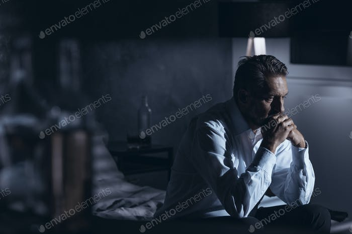Portrait of a lonely mature man with depression sitting on a bed