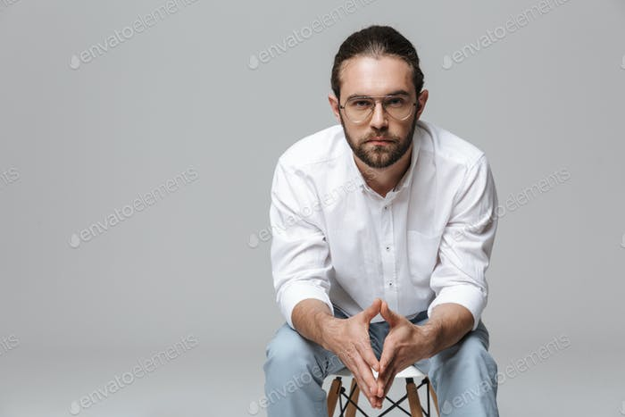 Handsome bearded man posing isolated over grey wall background.