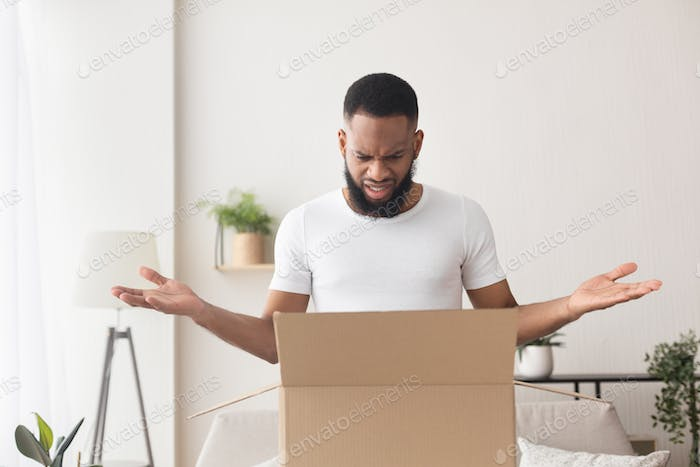 Surprised african american man opened box and spreads his hands