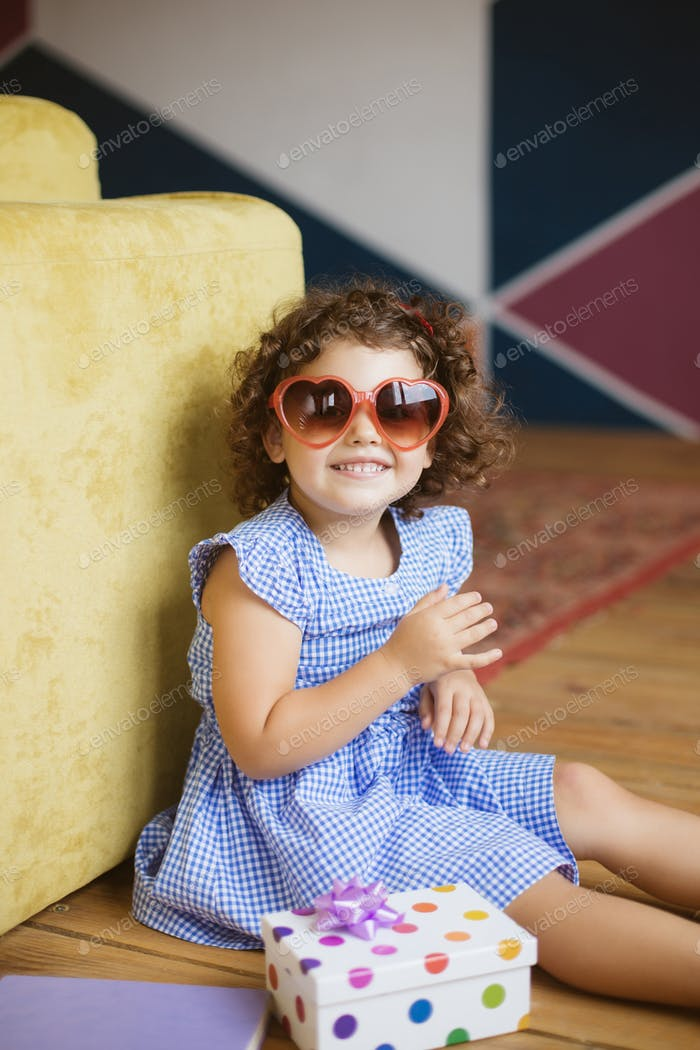 Cute little smiling girl with dark curly hair in dress and sungl