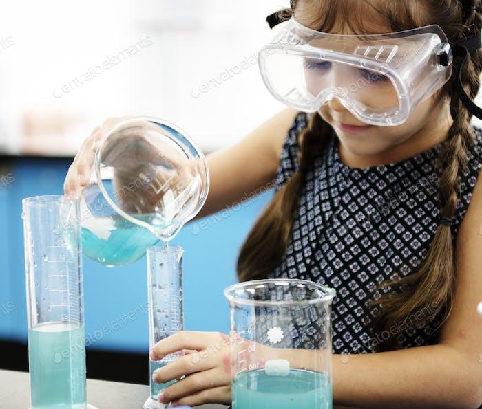 Kindergartenstudenten Mixing Solution in Science Experiment Labo