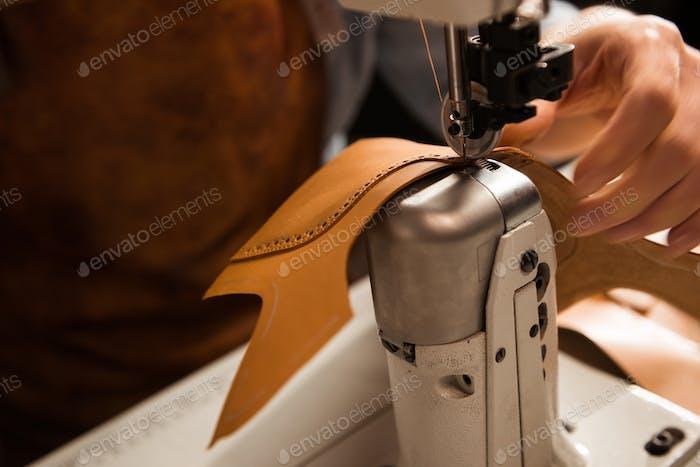 Nahaufnahme eines Schusters näht einen Teil des Schuhs