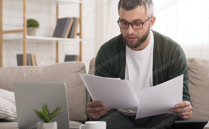 Mann hält Dokumente mit beiden Händen, liest es