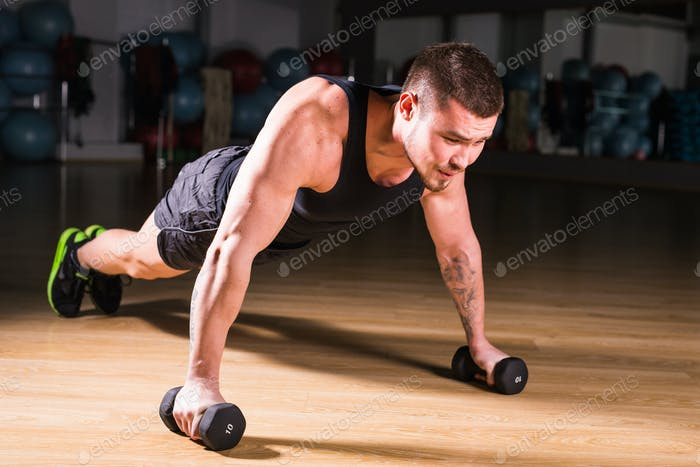 Gym man push-up strength pushup exercise with dumbbell in a fitness workout