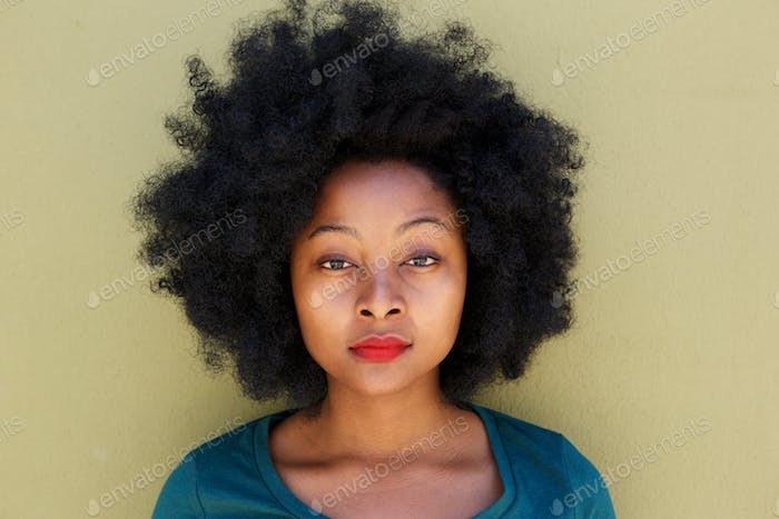 Close up serious young woman standing by wall with afro