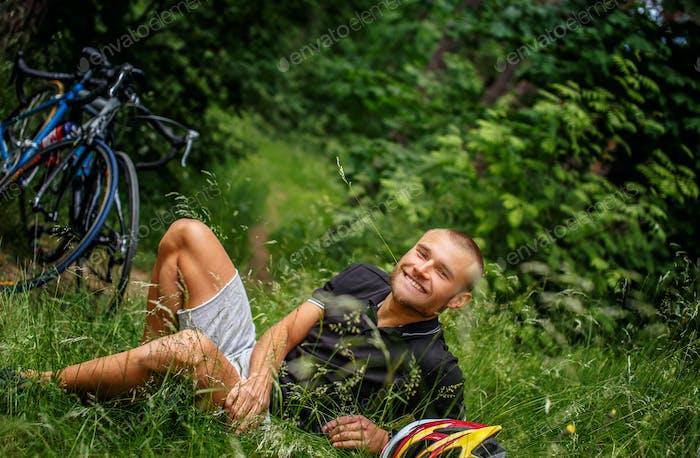 Un tipo sonriente tirado sobre el césped.
