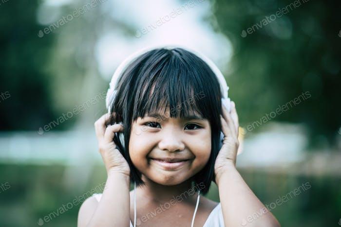 Маленькая девочка слушает музыку в парке
