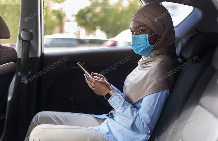Mujer de negocios musulmana negra usando máscara facial mientras usa taxi durante la pandemia de coronavirus