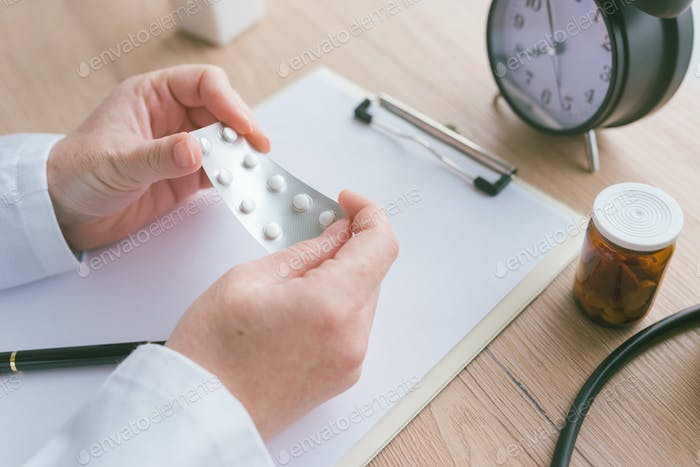 Female doctor holding unlabeled generic tablets