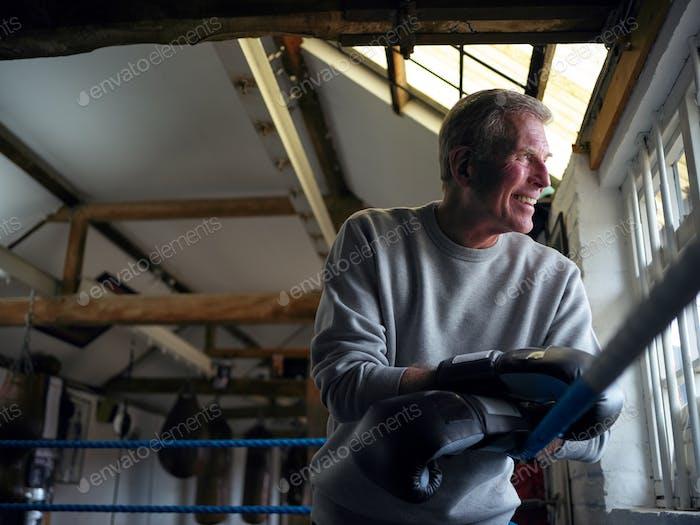 Smiling Senior Male Boxer In Gym Tragen Boxhandschuhe Lehnen Auf Seilen Von Boxring