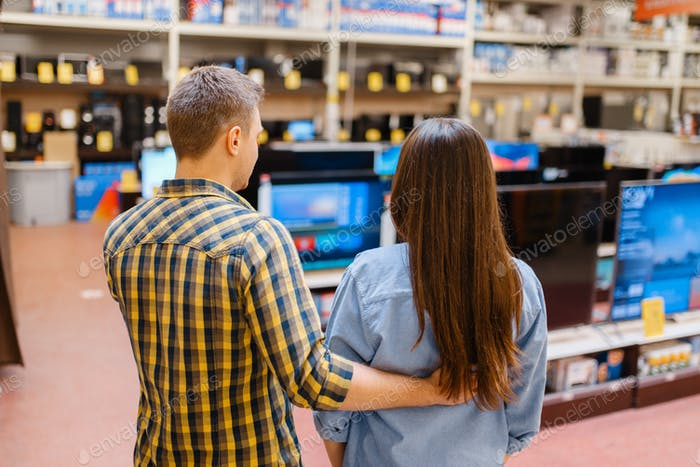 Couple choosing TV in electronics store