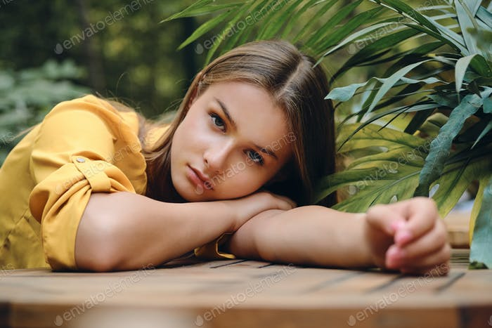 Young woman in yellow shirt lying on hand thoughtfully looking in camera among green leaves in park