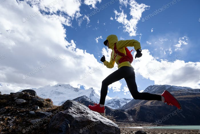 Woman trail runner cross country running in high altitude winter mountains