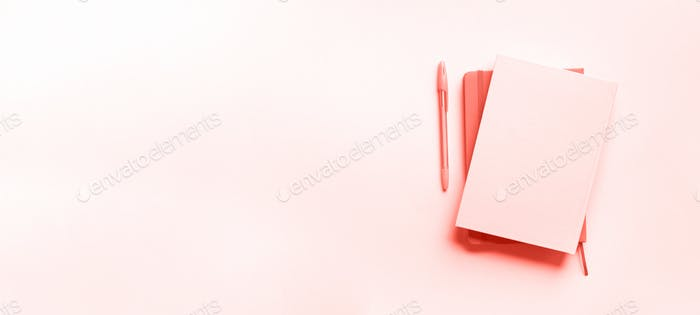 Top view of open notebooks on trendy coral color background. Copy space. Woman business, study, back