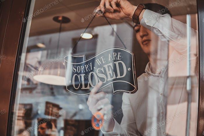 El hombre con camisa está poniendo una placa de identificación sobre cerrar en su propia tienda.