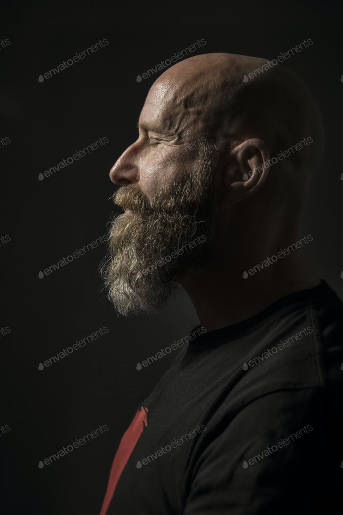 a bearded man with closed eyes side view and dark background