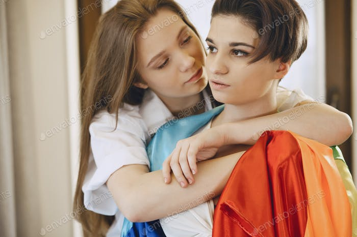 Lesbians hug and love each other with LGBT flag