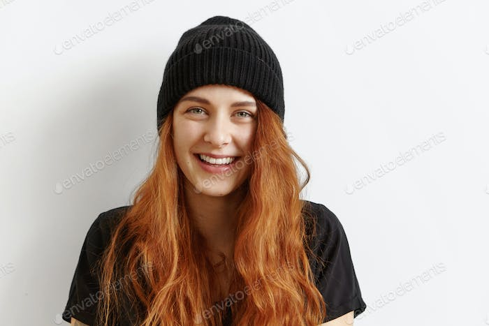 Close up shot of beautiful and charming young redhead European woman with messy loose hairstyle wear