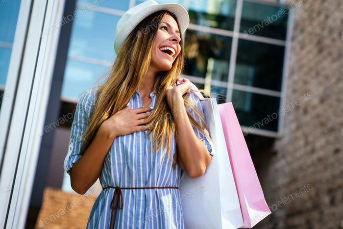 Glückliche Frau mit Tasche genießen in Shopping und Reisen. Konsum, Shopping, Lifestyle-Konzept