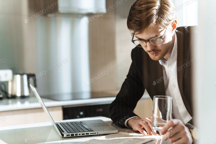 Foto von ernsthaften Geschäftsmann Lesen Zeitung während der Arbeit mit Laptop