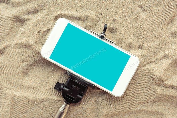 Smartphone auf Selfie-Stick im Strandsand