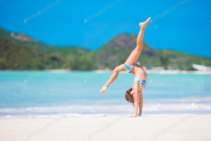 Active little girl at beach having a lot of fun. Sporty kid making the wheel on the seashore