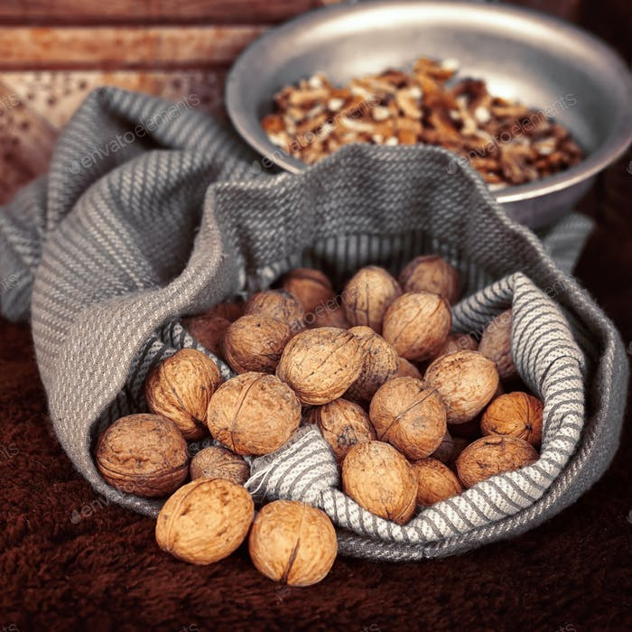 Whole walnuts in bag on the background walnut kernels in the bow