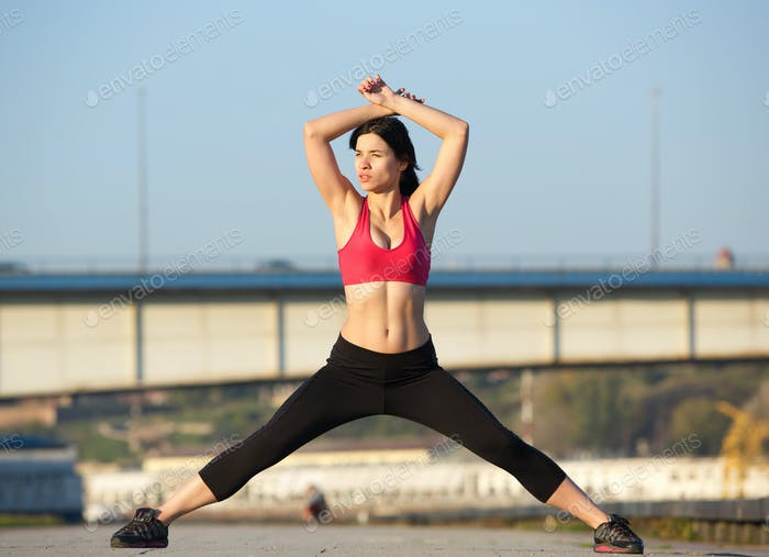 beautiful young woman wearing gym clothes and stretching muscles
