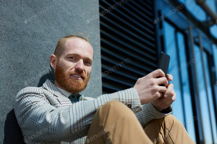 Portrait of bearded businessman with phone