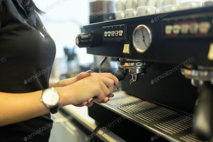 Barista making fresh coffee with machine