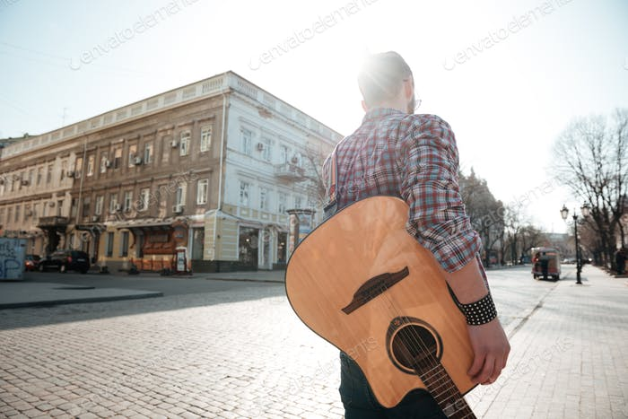 Man walking with guitar outdoors