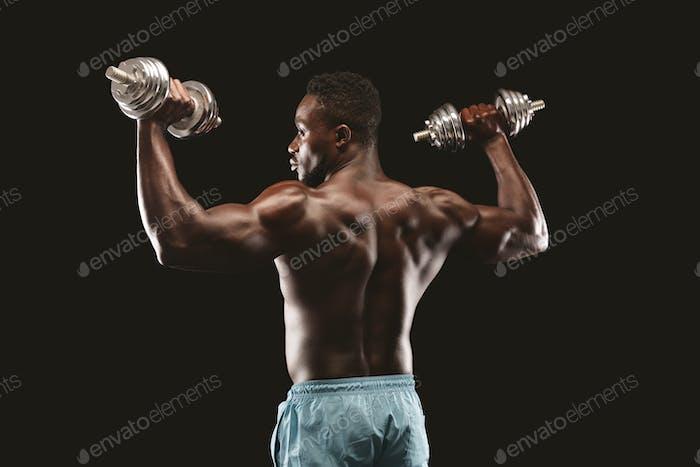 Black muscular athlete working out, pushing metallic barbells up