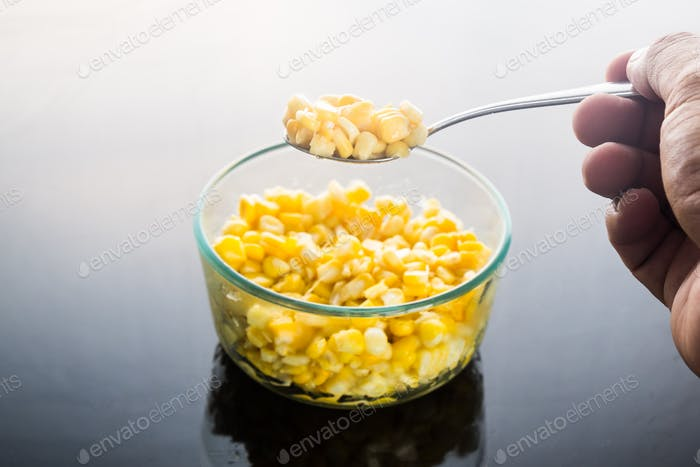Selective focus on spoonful of corn kernels against dark backgro