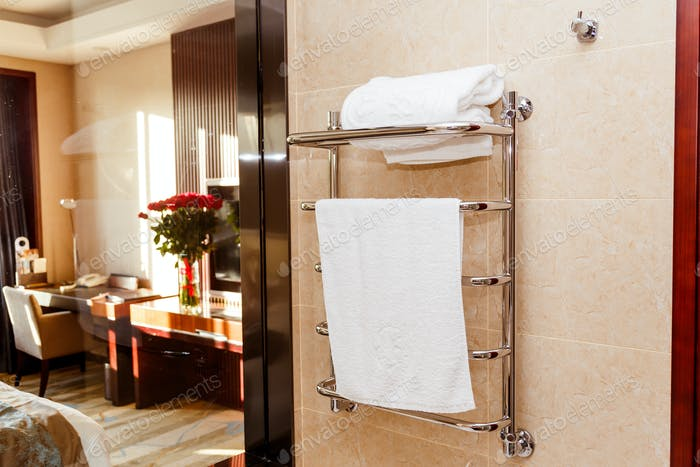Modern heated towel rail on tiled in hotel