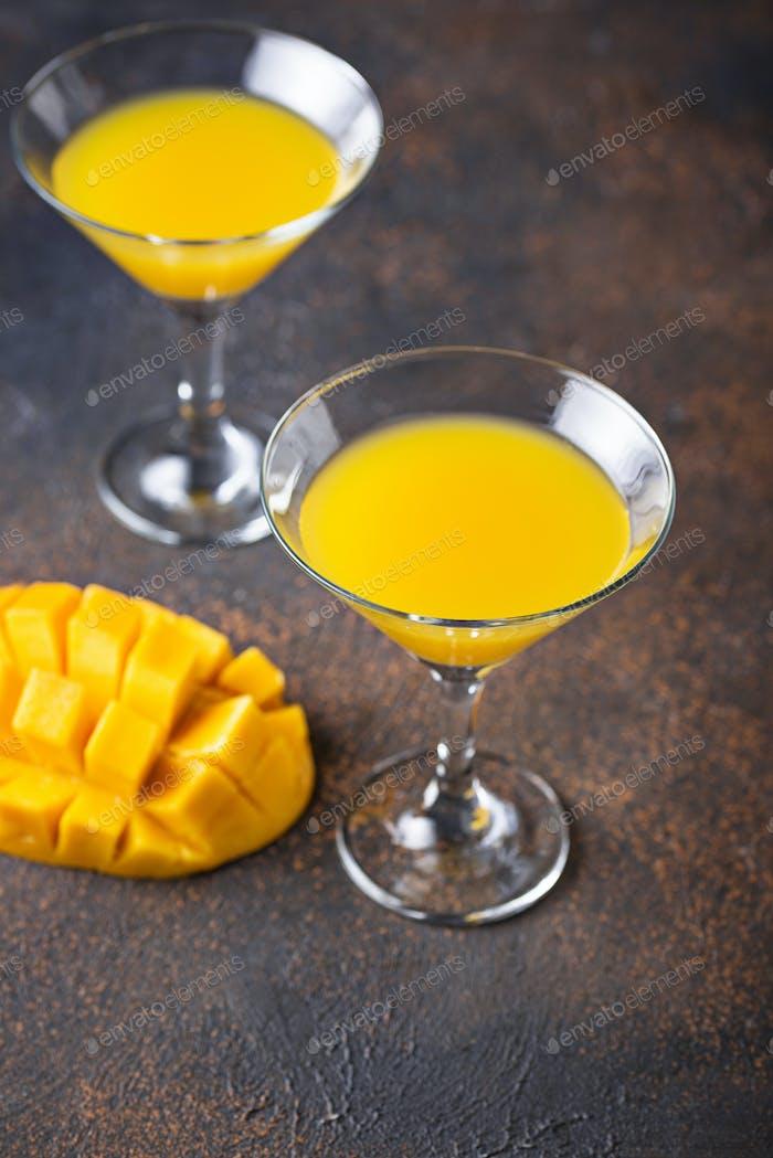 Tropischer Cocktail mit Mango auf dunklem Hintergrund