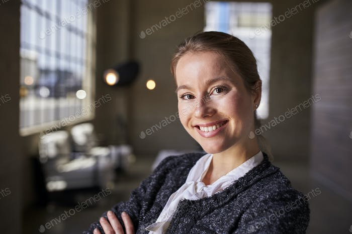 Young white businesswoman smiling to camera, close up